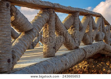 Wooden Fence Made Of Palm Trunks With Partly Cloudy Sky In Sunrise Time At Montaza Public Park In Su