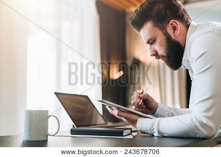 Young Bearded Businessman In Shirt Sitting At Desk In Front Of Laptop, Making Notes In Digital Table