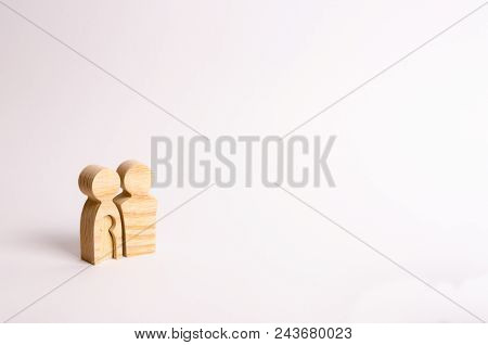 Wooden Figurines Of Parents Stand On A White Background. Concept Of Pregnancy, Young Family. Plannin