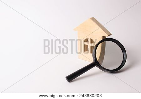 Wooden House And A Magnifying Glass On A White Background. The Concept Of Finding A House, Buying Or