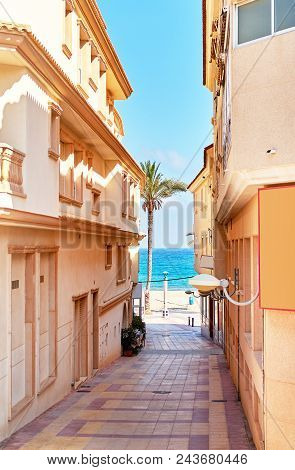 Narrow Street Of Spanish Town Of El Campello. Sunny Weather, Turquoise Colored Mediterranean Sea And