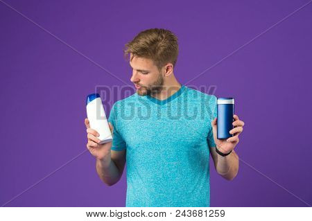 Man On Thoughtful Face Chooses Shampoo, Violet Background. Guy With Bristle Holds Two Bottles With S
