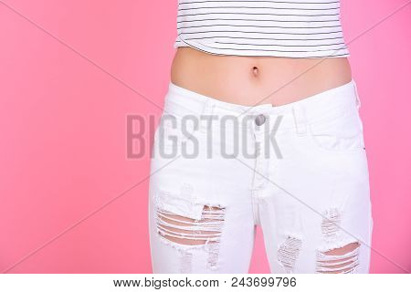 Slim Belly Of Woman In White Jeans On Pink Background, Copy Space. Dieting And Fitness Concept Shows