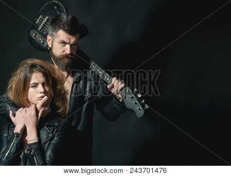 Couple In Love Cuddling With Guitar, Black Background. Rock And Roll Concept. Guitarist With Beard A