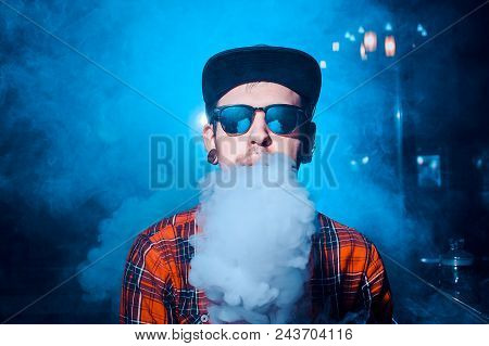 Punk Hipster Man Is Smoking A Mechanical Vape Device. Toned Image. The Concept Of Popularization Of