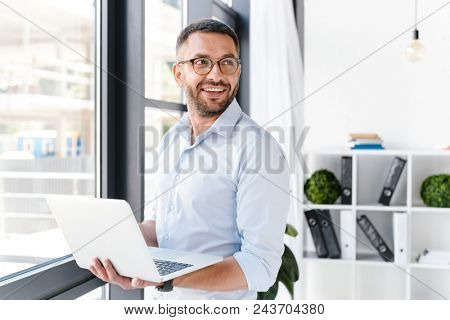 Image of office worker man wearing white shirt looking aside while holding silver laptop during work in business centre
