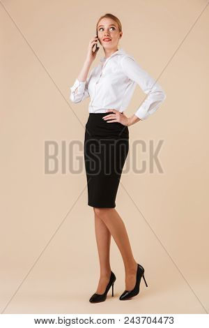 Full length portrait of a confident businesswoman talking on mobile phone isolated over beige background