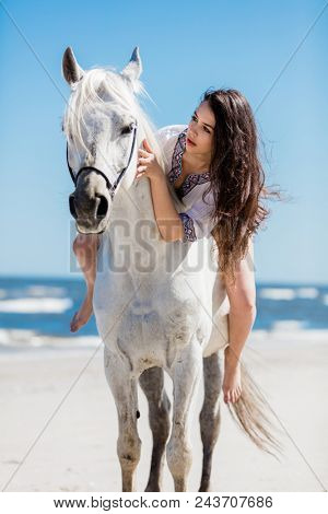 A portrait of a young girl sitting on a white horse on the beach. Bonding with animal.