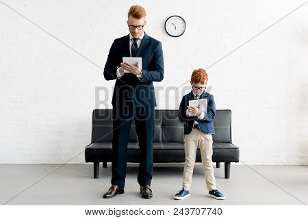 Father And Little Son Businessmen Using Digital Tablets Together