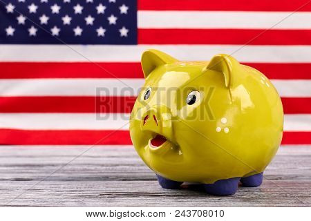 Money Box On Usa Flag Background. Yellow Piggy Bank On Old Wooden Table With Blurred American Flag I