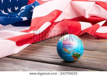 Globe And American Flag On Wooden Background. Usa Flag And Globe On Wooden Table Close Up. America A