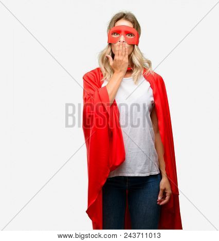 Young super hero woman wearing cape covers mouth in shock, looks shy, expressing silence and mistake concepts, scared