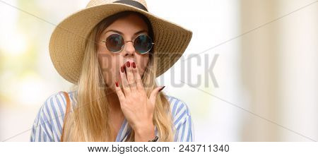 Young woman wearing sunglasses and summer hat covers mouth in shock, looks shy, expressing silence and mistake concepts, scared