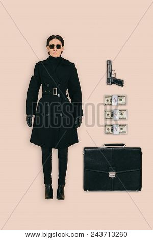 Top View Of Female Killer In Sunglasses With Briefcase, Handgun And Cash Isolated On Pink Background