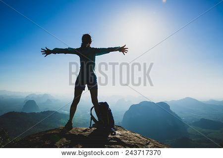 Successful Cheering Young Woman Hiker Outstretched Arms On Sunrise Mountain Peak Cliff Edge