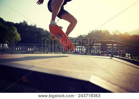 Closeup Of Skateboarder Legs Skateboarding On Skatepark Ramp