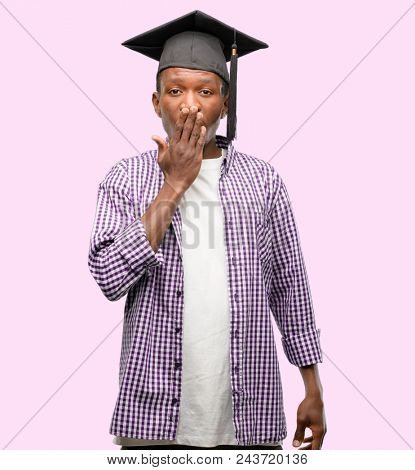 Young african graduate student black man covers mouth in shock, looks shy, expressing silence and mistake concepts, scared