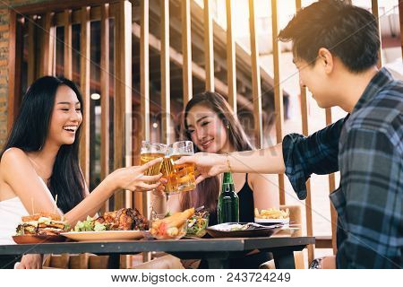 Asian People Cheering Beer At Restaurant Happy Hour And Laughing.