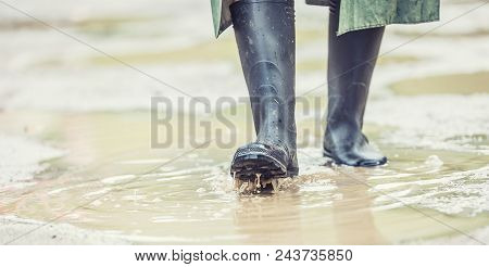 A Man With Black Boots Walks On A Flooded Road
