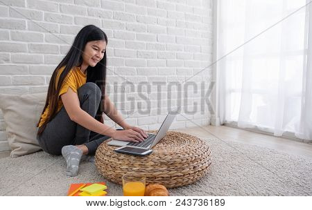 Asian Female Sit With Knees Up On Floor Using Laptop On Wicker Stand Near Window In Living Room At H