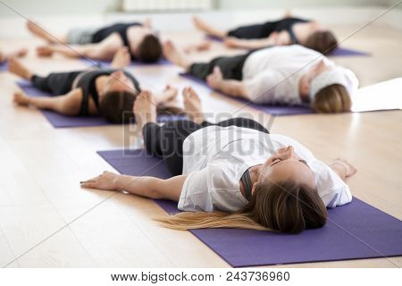 Group Of Young Sporty People Practicing Yoga Lesson, Doing Savasana, Dead Body Pose, Corpse Exercise