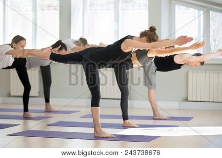 Group Of Young Sporty People Practicing Yoga Lesson, Doing Warrior Three Exercise, Virabhadrasana 3