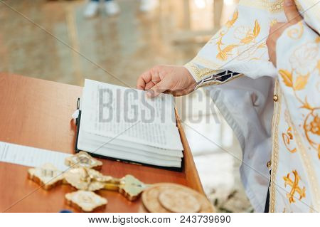 The Priest Blesses The Newlyweds. Bible, Cross On The Table. Priest During A Wedding Ceremony. Pries