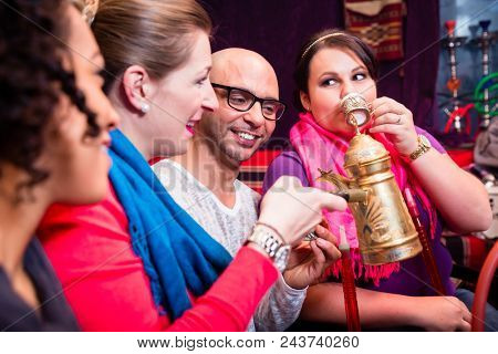 Group of friends smoking hookah and drinking coffee in shisha lounge enjoying themselves
