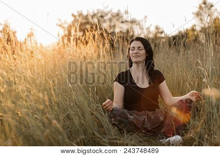 A Portrait Of A Woman Sitting In A Tall Grass With Her Eyes Closed And Meditating At Sunset. A Woman