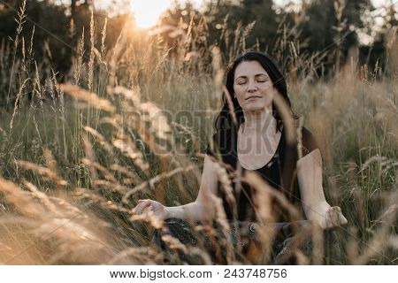 A Portrait Of A Woman Sitting In Tall Grass With Her Eyes Closed And Meditating At Sunset. A Woman R