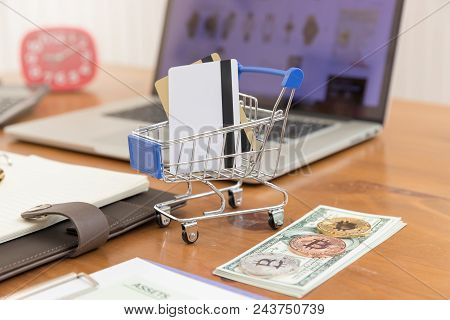 E-commerce Concept, Hand Holding Money And Credit Card In Shopping Cart With Laptop Open Shopping We