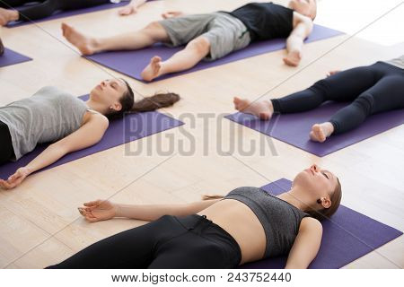 Group Of Young Sporty People Practicing Yoga Lesson, Doing Savasana Pose, Corpse Exercise, Dead Body