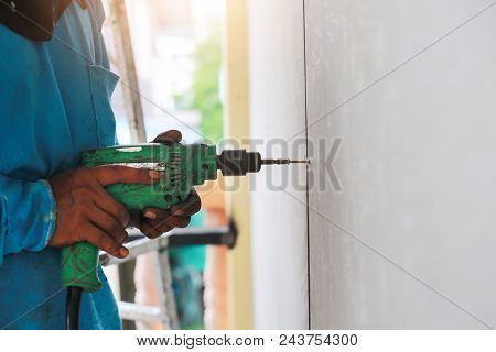 A Drilling Machine Is Making Hole On Wall Of Tiles.