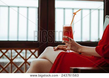 Close Up Of Woman In Red Dress With Red Cocktail With Orange Straw In Hands. Beautiful Girl In Red D