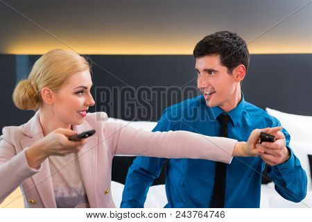 Happy couple switching TV with remote control in hotel room