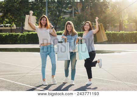 Group Of Young Asian Woman Shopping In An Outdoor Market With Shopping Bags In Their Hands. Young As