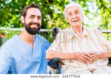 Nurse having chat with happy senior woman in nursing home