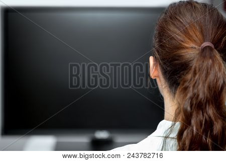 Young Woman Sitting In Front Of A Black Monitor Or Tv, Backview And Copyspace