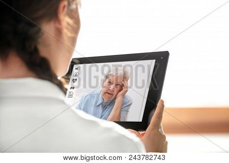 Diagnostic And Consultation With The Telemedicine, Doctor Holding A Tablet, Elderly Woman With Heada