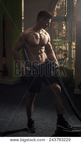Mens Heals Body Care. Sportsman, Athlete With Muscles Does Exercise With Ropes. Sport And Gym Concep