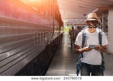 Backpacker And Hat At The Train Station And Looking On The Map For Plan To Travel, Young Traveler Wi