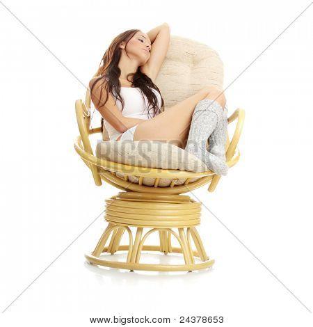 Schöne junge Frau im Sessel ausruhen. Isoliert auf weißem Hintergrund