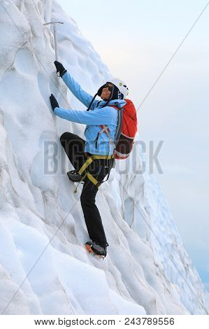 Young Woman Dressed In A Blue Jacket And Helmet On Her Head Climbing On The Icy Top Of Falljokull Gl