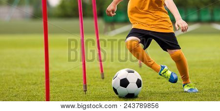 Soccer Player With Soccer Ball Running Slalom Around Training Sticks. Football Speed Training. Young