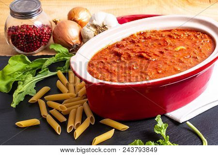 Homemade slow cooker bolognese sauce in red ceramic pot and raw penne, peppercorn, garlic, onion and rocket salad poster