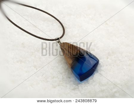 Hand Made Pendant Of Blue Color On White Crystal Background. Bijouterie Made Of Epoxy Resin And Wood