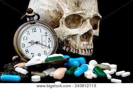 Antique Clock On Multicolored Of Drug And Capsule Behind Clock Is A Skull. Is On The Black Backgroun