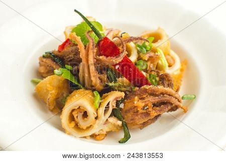 Fried Squids Calamari, Chili Pepper And Mint Leaves On White Plate