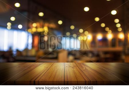 Empty Wooden Table Top With Blur Coffee Shop Or Restaurant Interior Background. Abstract Background