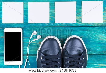 Overhead View Of Sports Shoes By Mobile Phone With Isolated Screen And In-ear Headphones And White E